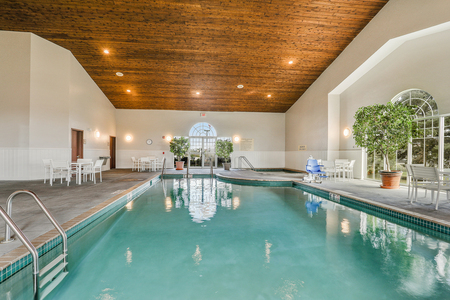 Sparkling indoor pool surrounded by white chairs and greenery