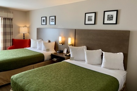 Guest room featuring a red armchair and two queen beds with green linens