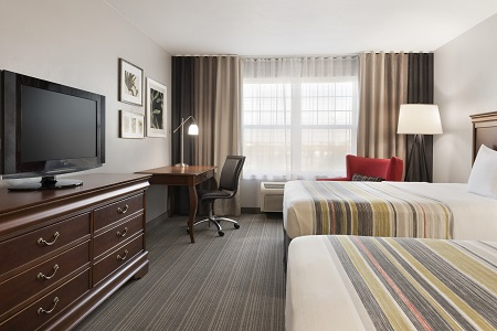 Hotel room with two beds, armchair, desk and TV