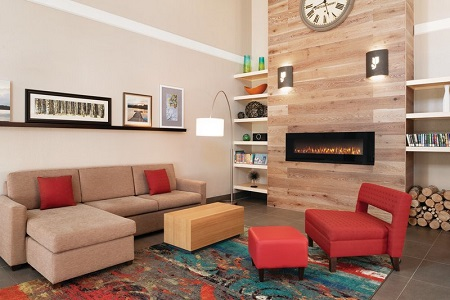 Spacious lobby with a fireplace, red armchair, tan sectional and multicolored rug