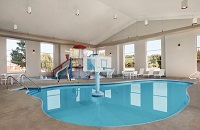 Indoor pool with a basketball hoop and a waterslide play area