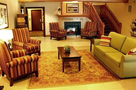 Hotel lobby with green sofa, striped armchairs and fireplace