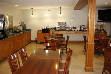 Breakfast room with tables, chairs and wooden cabinetry