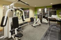 Fitness equipment beside a mirror and TV in upper right corner