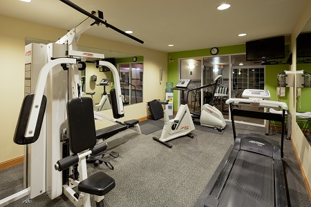 Fitness equipment in room with mirror and TV