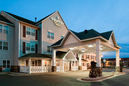Exterior of the Country Inn & Suites lit up at dusk