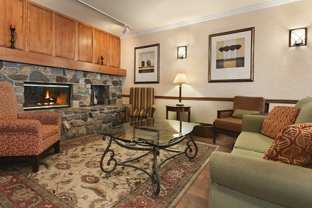 Comfortable lobby with a fireplace, a patterned carpet and plush seating