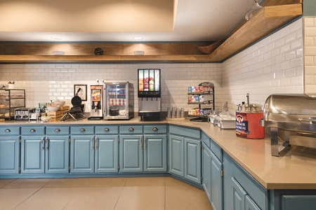 Breakfast area with blue cabinets, hot entrées, oatmeal, juice and a waffle iron