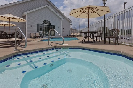 Outdoor pool and hot tub surrounded by patio furniture with white umbrellas