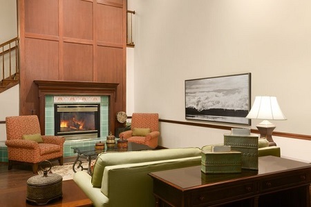 Welcoming hotel lobby with a fireplace, a couch and two red armchairs