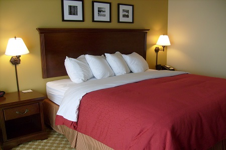Charleston hotel room featuring a king bed with a red comforter