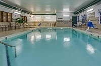 Hotel's indoor pool area with white chairs