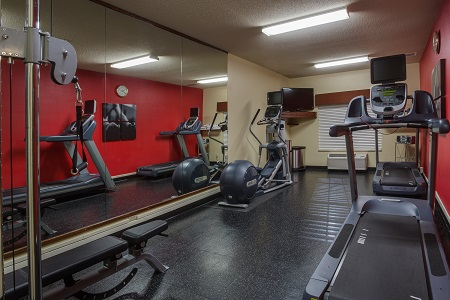 Hotel fitness center with two treadmills and a red accent wall