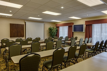 Rows of tables and chairs facing a projector screen in the hotel's meeting room