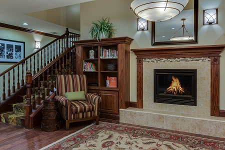Welcoming hotel lobby with a fireplace, bookshelves and a chair by the stairs