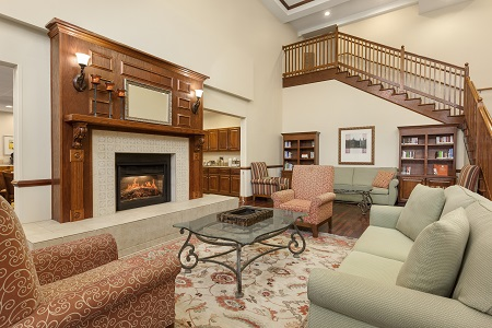 Hotel lobby with fireplace, chairs and wooden staircase