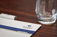 Water glass beside notepad with Park Plaza logo