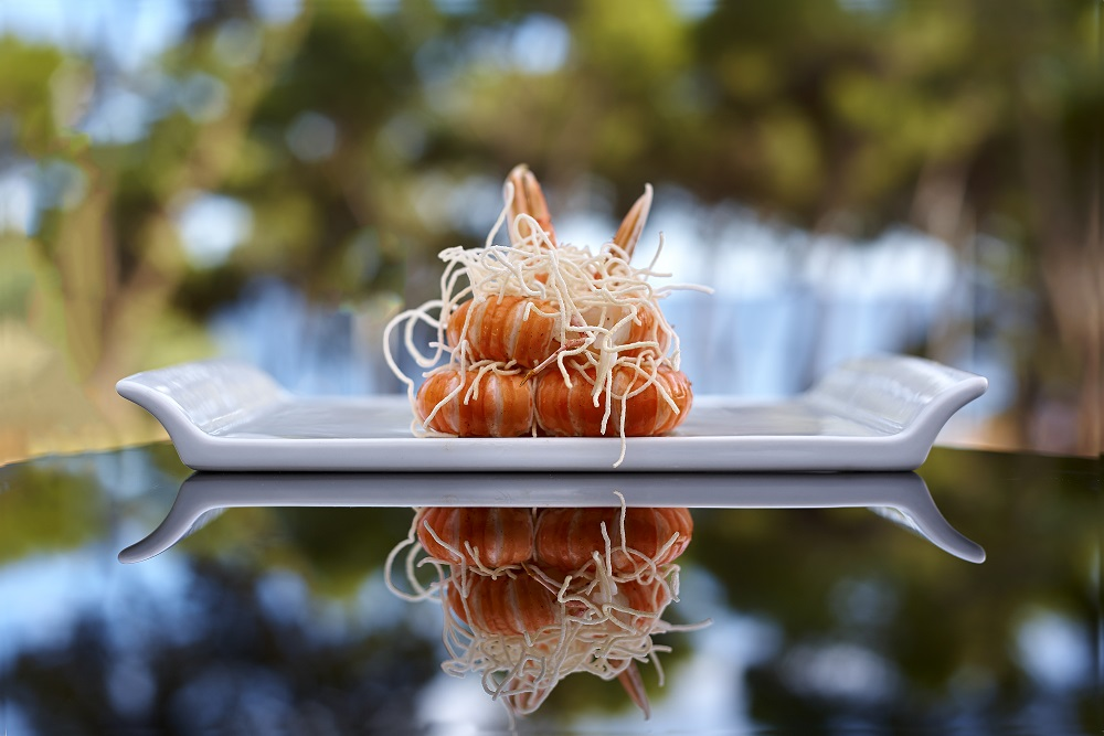 Elegant shrimp entree on reflective outdoor table