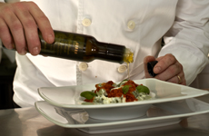 Chef drizzles sauce on dish during Istrian cuisine week