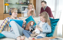 Children playing with dolls and tablet on couch while parents watch