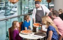 Waiter serving pizza to family