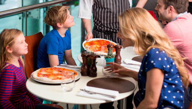 Server delivering pizza to table with two kids and two adults