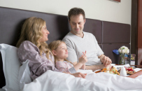 Family in bed together in London hotel room