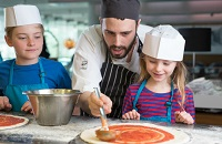 Chef helping kids make pizza