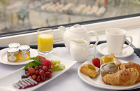 Breakfast of fruit, jam, croissant and more