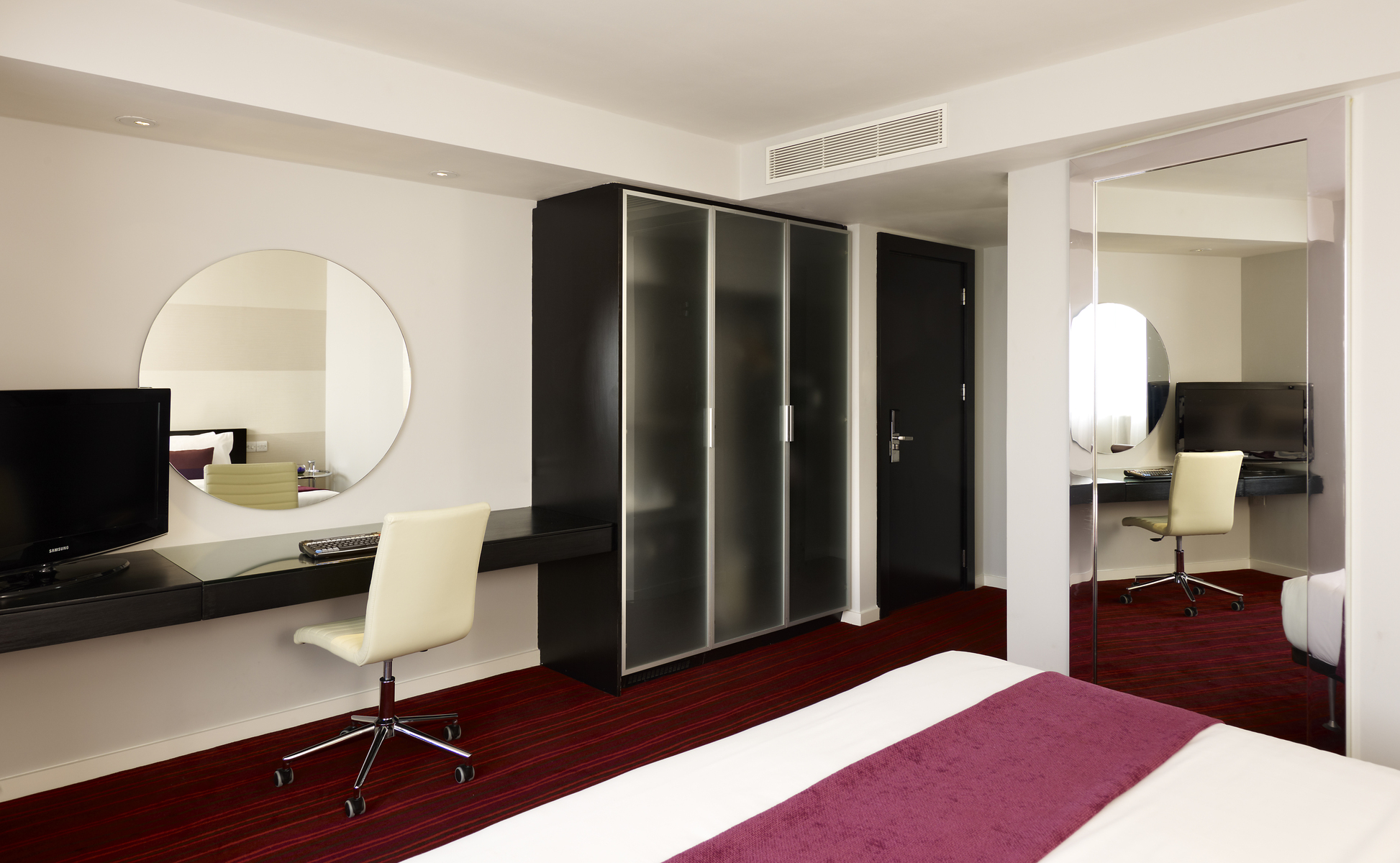 Leeds hotel room with work desk and circular mirror
