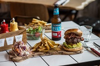 Burger, beer, fries, condiments and place setting