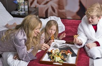 Mother and two children eating waffles, pancakes and fruit in bed