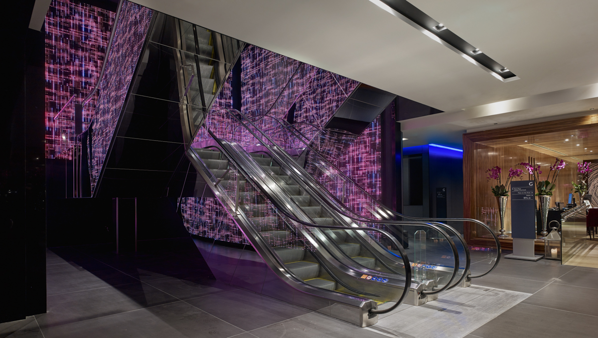 Welcoming lobby with escalator at London riverbank hotel