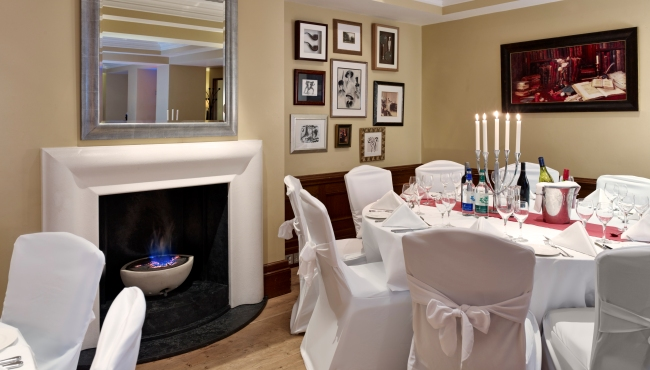 Fireplace and elegant table setting in banquet room