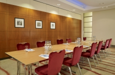 Long meeting room table with red chairs
