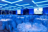 Blue-lit ballroom with round tables