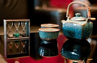 Teal teapot and teacups next to hourglass decoration