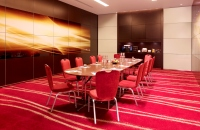 Red chairs surrounding long table in meeting room