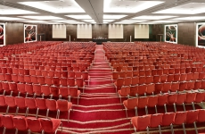 Many rows of red chairs in large conference space