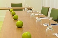 Conference table set with notepads, pens, apples and water glasses