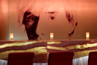 Candles on bar in front of mural of Andy Warhol's face