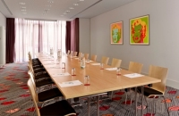 Long wooden meeting table with Warhol art on wall