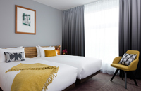 Two white beds with yellow blanket and grey and yellow pillows