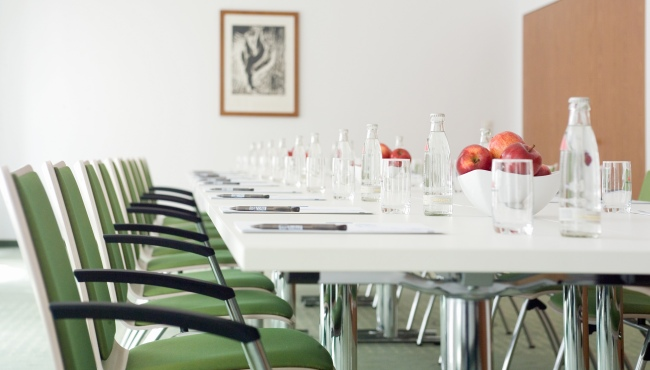 Meeting room with green chairs, table, apples and bottles of water