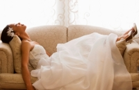 Bride reclining on sofa in her wedding dress