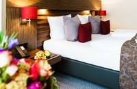 Hotel room featuring a comfortable bed with red and grey pillows and fruit on the bedside table