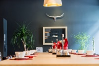Modern dining area with leafy table decor and large bowls