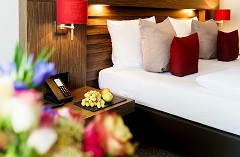 Guest room featuring a comfortable bed with red and grey pillows and fruit on the bedside table