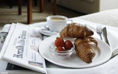 Newspaper beside two croissants on a plate and a small bowl of strawberries
