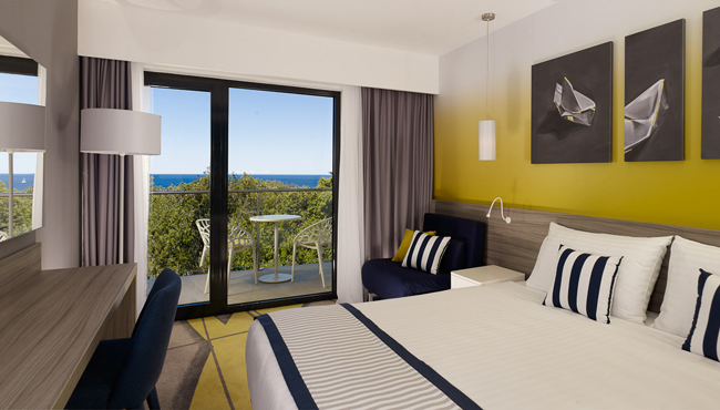 Seaside hotel room with a white-and-navy bed